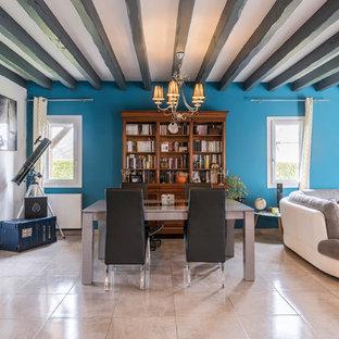 Réalisation d'une salle à manger ouverte sur le salon bohème avec un mur bleu et un sol beige.