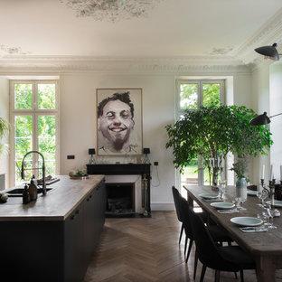他の地域の大きいエクレクティックスタイルのおしゃれなダイニングキッチン (茶色い床、白い壁、無垢フローリング、標準型暖炉、石材の暖炉まわり) の写真