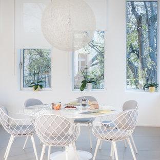 Exemple d'une salle à manger ouverte sur le salon bord de mer de taille moyenne avec un mur blanc et béton au sol.