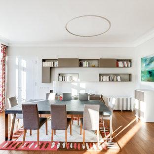 Aménagement d'une grand salle à manger contemporaine fermée avec un mur blanc, un sol en bois brun et aucune cheminée.