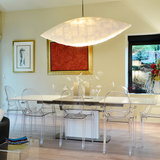 Cette photo montre une salle à manger ouverte sur le salon tendance de taille moyenne avec un mur jaune et un sol en bois clair.