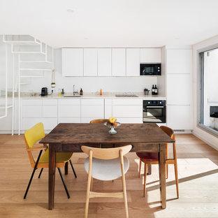Idée de décoration pour une salle à manger ouverte sur le salon design avec un mur blanc, aucune cheminée, un sol marron et un sol en bois clair.