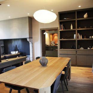 Cette photo montre une grand salle à manger ouverte sur le salon tendance avec un sol en bois brun et un mur blanc.