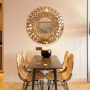 Exemple d'une salle à manger tendance fermée avec un mur beige et un sol en bois clair.