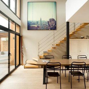 Idée de décoration pour une grand salle à manger ouverte sur le salon design avec un mur beige, un sol en bois clair et aucune cheminée.