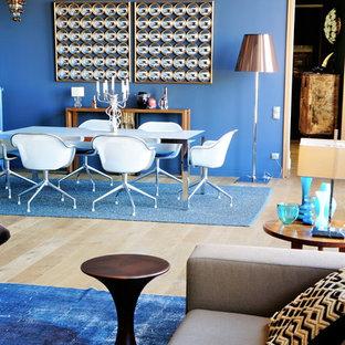 Exemple d'une salle à manger ouverte sur le salon tendance de taille moyenne avec un mur bleu et un sol en bois clair.