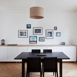 Idée de décoration pour une grande salle à manger design fermée avec un mur blanc, un sol en bois brun et aucune cheminée.