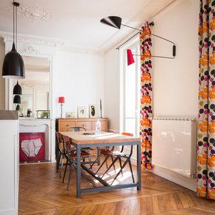 Cette image montre une salle à manger design fermée et de taille moyenne avec un mur blanc, un sol en bois brun, une cheminée standard et un manteau de cheminée en pierre.