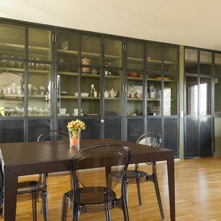 Cette photo montre une salle à manger ouverte sur le salon tendance de taille moyenne avec un mur vert et un sol en bois brun.