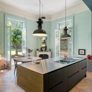 Inspiration för mellanstora matplatser med öppen planlösning, med gröna väggar, ljust trägolv, en öppen hörnspis, en spiselkrans i trä och beiget golv