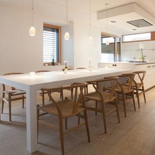 Idées déco pour une grand salle à manger ouverte sur la cuisine contemporaine avec un mur blanc, un sol en bois clair et aucune cheminée.