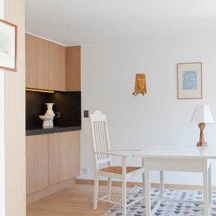 Inspiration pour une salle à manger ouverte sur la cuisine design de taille moyenne avec un mur blanc et un sol en bois clair.