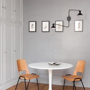 Idée de décoration pour une salle à manger design de taille moyenne et fermée avec un mur gris, un sol en bois brun et aucune cheminée.