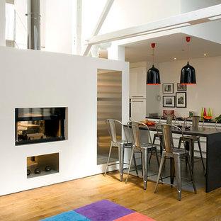 Inspiration pour une salle à manger ouverte sur le salon urbaine avec un mur blanc, un sol en bois brun et une cheminée double-face.