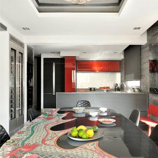 Aménagement d'une salle à manger ouverte sur la cuisine éclectique avec un mur gris.
