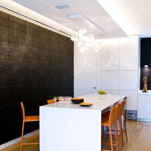 Réalisation d'une grande salle à manger ouverte sur le salon design avec un sol en bois clair et un mur noir.