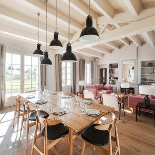 Пример оригинального дизайна: большая гостиная-столовая в скандинавском стиле с белыми стенами и паркетным полом среднего тона