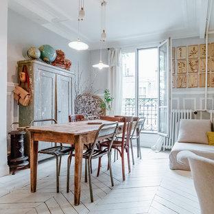 Aménagement d'une salle à manger ouverte sur le salon éclectique de taille moyenne avec un mur gris et un sol en bois peint.