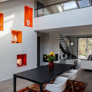 Imagen de comedor ecléctico, de tamaño medio, abierto, con paredes grises, marco de chimenea de yeso, suelo gris y chimenea de doble cara