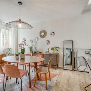 Exemple d'une salle à manger ouverte sur le salon tendance de taille moyenne avec un mur blanc, aucune cheminée, un sol en bois clair, un sol beige et du papier peint.