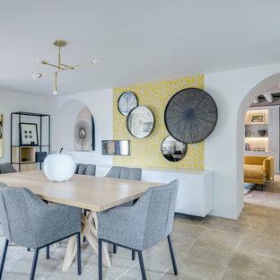 Cette photo montre une salle à manger chic avec un mur jaune et un sol en travertin.
