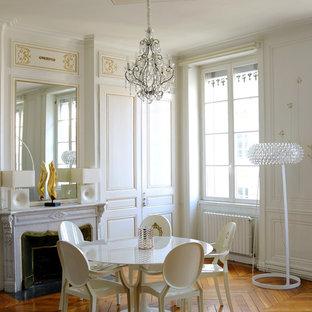 Exemple d'une salle à manger ouverte sur le salon chic de taille moyenne avec un mur blanc, un sol en bois brun, une cheminée standard et un manteau de cheminée en pierre.