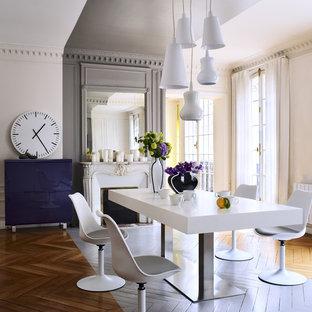 Inspiration pour une grande salle à manger design fermée avec un mur beige, une cheminée standard, un manteau de cheminée en pierre et un sol en bois peint.
