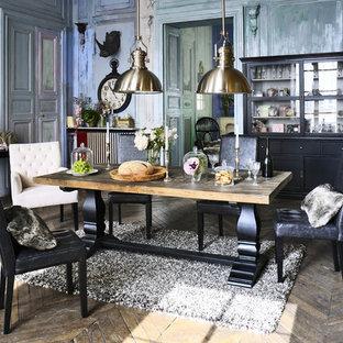 Réalisation d'une grande salle à manger champêtre fermée avec un sol en bois brun, une cheminée standard, un mur multicolore et un manteau de cheminée en métal.