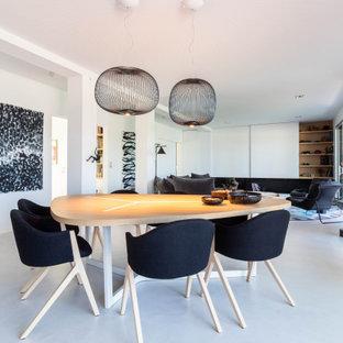 Aménagement d'une salle à manger ouverte sur le salon contemporaine avec un mur blanc, béton au sol et un sol blanc.