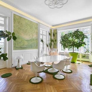 Inspiration pour une salle à manger design avec un mur vert, un sol en bois brun, une cheminée standard, un manteau de cheminée en pierre et un sol marron.