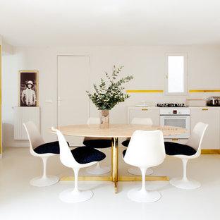 Cette image montre une grande salle à manger ouverte sur la cuisine design avec un mur blanc et un sol blanc.