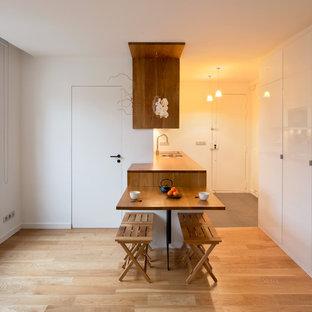 Cette photo montre une petit salle à manger ouverte sur la cuisine tendance avec un mur blanc, un sol en bois clair et aucune cheminée.