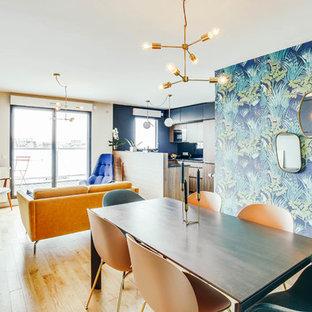 Exemple d'une salle à manger tendance de taille moyenne avec un mur bleu, un sol en bois clair, une cheminée standard, un manteau de cheminée en métal et un sol beige.