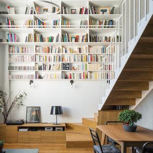 Idée de décoration pour une salle à manger ouverte sur le salon design avec un mur blanc, un sol en bois clair et un sol beige.