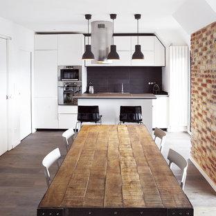 Exemple d'une grande salle à manger ouverte sur la cuisine tendance avec un mur blanc et un sol en bois brun.