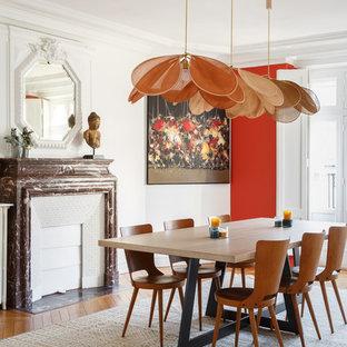 Réalisation d'une grand salle à manger bohème fermée avec un mur blanc, un sol en bois brun, une cheminée standard, un manteau de cheminée en pierre et un sol marron.