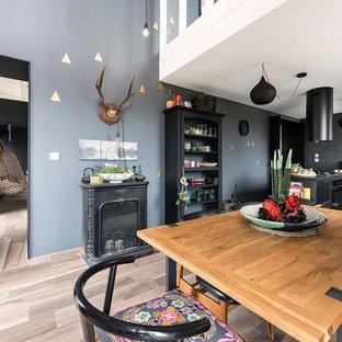 Idée de décoration pour une salle à manger ouverte sur la cuisine bohème de taille moyenne avec un mur gris, un sol en bois clair et une cheminée standard.
