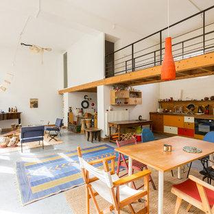 Réalisation d'une grand salle à manger ouverte sur le salon bohème avec un mur blanc, béton au sol et aucune cheminée.