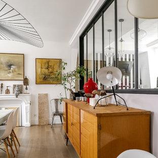 Réalisation d'une salle à manger bohème fermée avec un mur blanc, un sol en bois brun, une cheminée standard et un sol marron.