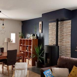 Ispirazione per una sala da pranzo aperta verso il soggiorno moderna di medie dimensioni con pareti blu, pavimento con piastrelle in ceramica, stufa a legna, cornice del camino in pietra ricostruita e pavimento grigio