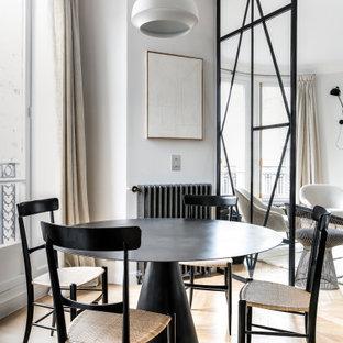 Cette image montre une salle à manger design avec un mur gris, un sol en bois brun et un sol marron.
