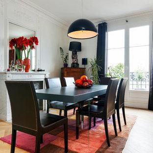 Inspiration pour une salle à manger ouverte sur le salon nordique avec un mur blanc, un sol en bois clair et une cheminée standard.