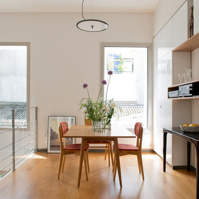Inspiration for a mid-sized contemporary medium tone wood floor great room remodel in Paris with white walls