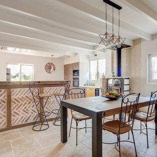 Idee per una sala da pranzo aperta verso la cucina minimal di medie dimensioni con pareti gialle, pavimento in travertino, stufa a legna e pavimento beige