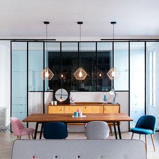 Aménagement d'une salle à manger ouverte sur le salon scandinave avec un mur blanc, un sol en bois clair et un sol beige.