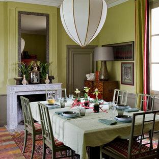 Cette photo montre une grande salle à manger exotique fermée avec un mur vert, une cheminée standard et un manteau de cheminée en pierre.