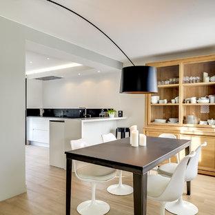 Exemple d'une salle à manger ouverte sur le salon tendance de taille moyenne avec un mur blanc, un sol en bois clair et aucune cheminée.