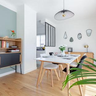 Cette photo montre une salle à manger scandinave avec un mur blanc, un sol en bois clair et un sol beige.