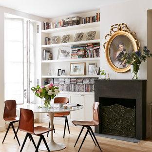 Exemple d'une salle à manger scandinave avec un mur blanc, une cheminée standard, un sol en bois clair et un manteau de cheminée en plâtre.
