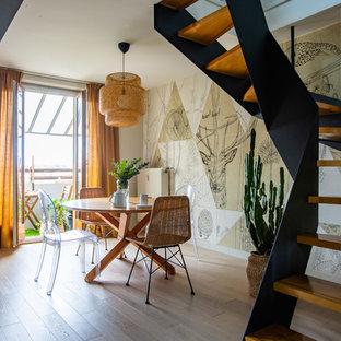 Aménagement d'une salle à manger ouverte sur le salon éclectique de taille moyenne avec un mur beige, un sol en bois clair, un sol beige et aucune cheminée.
